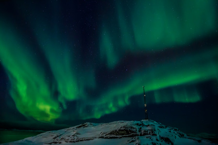 nuuk: Radio tower on the hill and the Northern lights over the fjord in the background, Nuuk Greenland