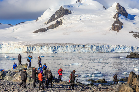 Group of tourists looking at the glacier at the stony shore of Half Moon Island, Antarctic