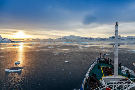 Sunset view and people gathered on the deck, Icebergs drifting at Lemaire Channel, Antarctica