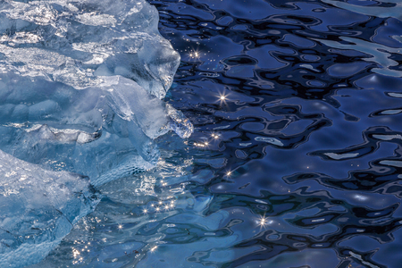 Drifting piece of blue iceberg and sun glaring on the water surface, Greenland Stock Photo