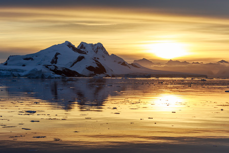 Sunset over the mountains and drifting icebergs at Lemaire Strait, Antarctica Stock Photo