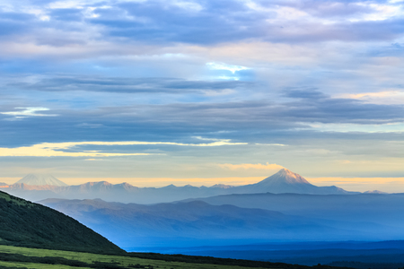 Green valley covered with clouds with smoking volcanoes in background Stock Photo