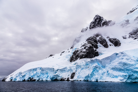 Huge steep stone rock covered with blue glacier and cloud with water in foreground, close to Argentine islands, Antarctica cruise