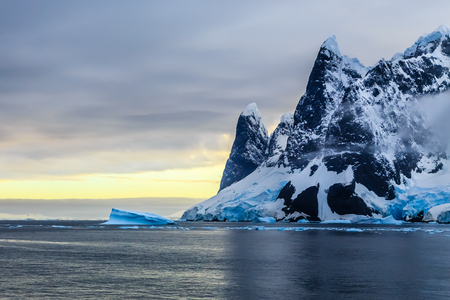 Sunset over cliffs, blue glacier and drifting iceberg with water surface in foreground, close to Argentine islands, Antarctica