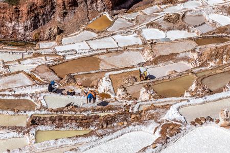 Workers doing  their hard job on salt mines and basins, Salineras de Maras. Peru