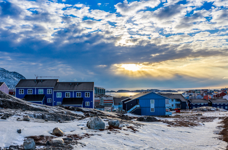 greenlandic: Polar sunset over Inuit houses on the rocky hills with snow, Nuuk city, Greenland Stock Photo