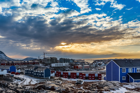 greenlandic: Arctic houses growing on the rocky hills in sunset panorama. Nuuk, Greenland