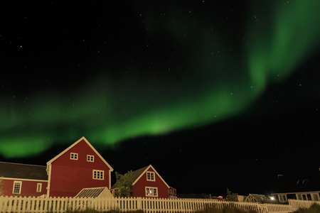 greenlandic: Northern lights and starlight sky over two red living houses, Nuuk, Greenland Stock Photo