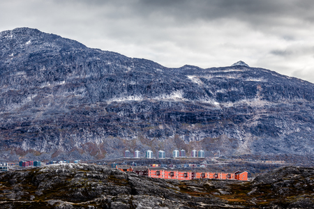 greenlandic: Rows of colorful modern Inuit houses among mossy stones with grey steep slopes of Little Malene mountain in the background, Nuuk, Greenland