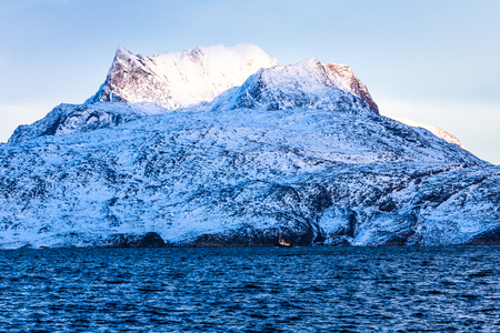 nuuk: Huge Sermitsiaq mountain covered in snow with blue sea and small fidhing boat in the foreground, nearby Nuuk city, Greenland