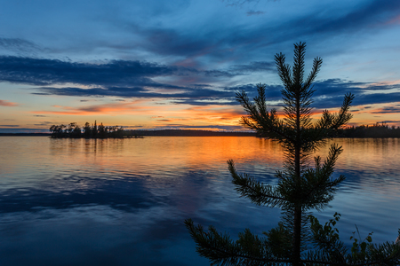 Orange sunset over the island and lake surface during the white nights in Karelia