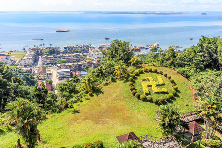 Sandakan town landscape with green lawn in Hindu counterclockwise swastika shape and blue Sulu sea in the background, Borneo, Malaysia