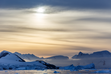 Sunset over the mountains with glaciers and drifting icebergs at Lemaire Strait, Antarctica Stock Photo