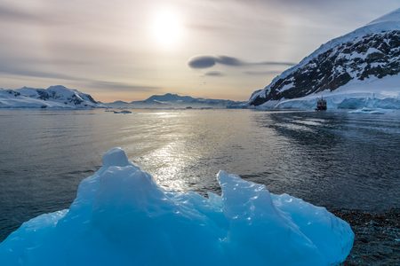 Big blue piece of iceberg with lagoon in the background, Neco bay, Antarctica Stock Photo