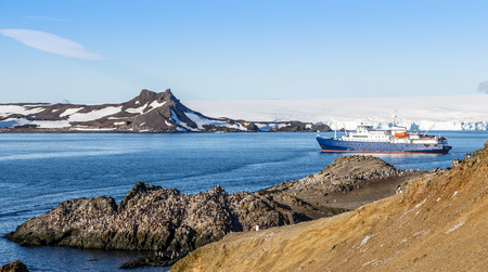 Blue antarctic cruise ship in the lagoon and Gentoo penguins colony on the rocky shore of the Barrientos Island, Antarctica
