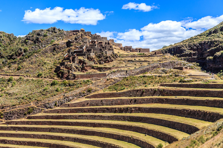 Ruins of ancient Incan city with terraces on the mountain with cloud sky in the background, Pisac, Peru