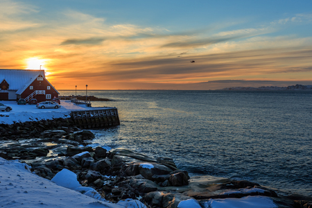 Nuuk city rocky coastline in snow, old sea harbor sunset view, Greenland Banco de Imagens
