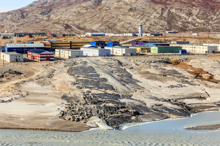 Living blocks on the hill above muddy melted glacier river with airport in the background, Kangerlussuaq settlement, Greenland