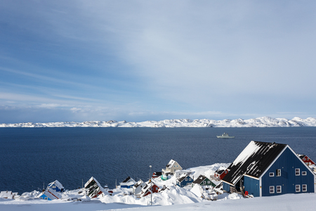 Covered in snow inuit houses at the fjord with drifting ship, Nuuk, Greenland