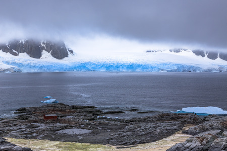 Rocky coastline fjord panorama with mountains, clouds and blue glacier, Peterman island, Antarctic peninsula Stock Photo