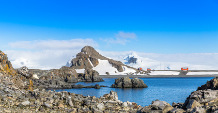 Rocky coastline panorama with snow mountains and polar research station buildings, Half Moon island, Antarctic peninsula