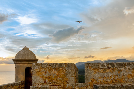 Aircraft landing over San Pedro de La roca fort walls and tower, sunset view, Santiago De Cuba, Cuba