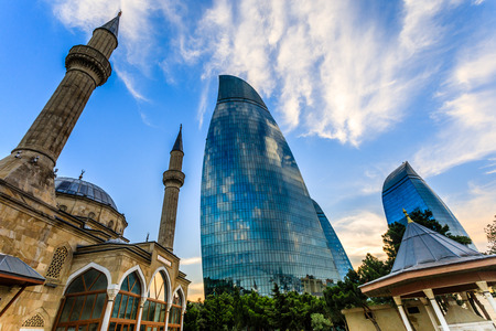 Turkish mosque of the Martyrs and modern glass central business district skyscrapers in the sunset, Baku, Azerbaijan