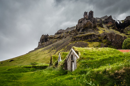 Icelandic turf houses covered with grass and cliffs in the background near Kalfafell vilage, South Iceland