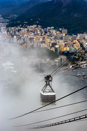 Cable car in the clouds on its way to the top of SugarLoaf, and city panorama of Rio de Janeiro, Brazil Banco de Imagens
