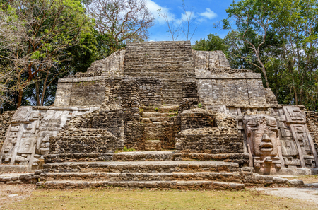 Old ancient stone Mayan pre-columbian civilization pyramid with carved face and ornament hidden in the forest, Lamanai archeological site, Orange Walk District, Belize 스톡 콘텐츠 - 99563065
