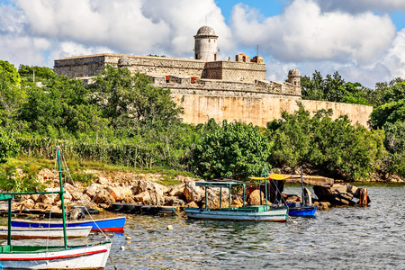 Jagua castle fortified walls with trees and fishing boats in the foreground, Cienfuegos province, Cuba Editorial