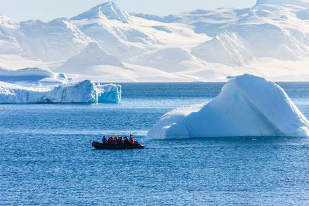 Barco lleno de turistas que pasan por los enormes icebergs en la bahía cerca de la isla Cuverville, Península Antártica.