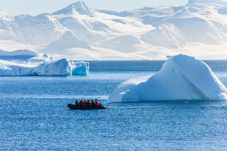 Boat full of tourists passing by the huge icebergs in the bay near Cuverville island, Antarctic peninsula