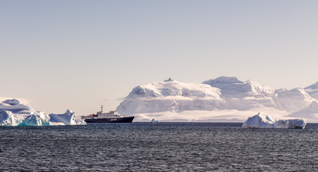 Touristic cruise liner among blue icebergs close to Cuverville Island, Antarctic