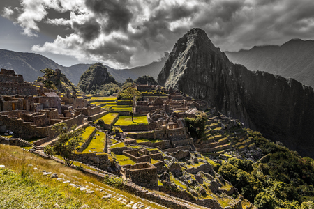 Panoramic view to old Inca ruins and Wayna Picchu with grey clouds in the background, Machu Picchu archaeological site, Urubamba provnce, Peru