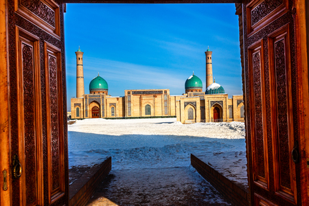 Winter shot of blue domes, mosques and minarets of Hazrati Imam medrese with wooden ornated doors in the foreground, religious center of Tashkent, Uzbekistan