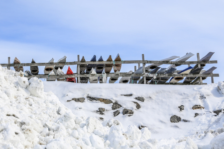 Rows of Inuit kayaks stored for a winter time, Nuuk old city harbor, Greenland