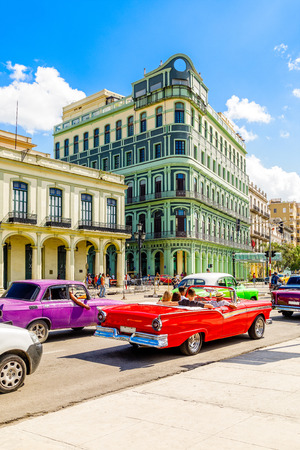 Old colonial buildings across the road with driving retro red cabriolet car in the center of Havana, Cuba