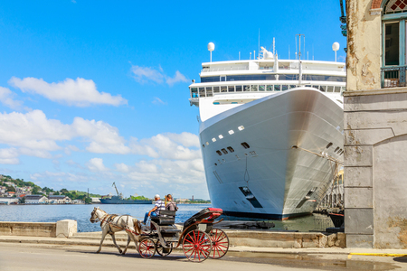 Big cruise ship docked around the corner of the street and horse carriage on the road, port of Havana, Cuba Standard-Bild - 118372557