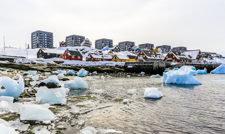 Modern buildings and small cottages with icebergs drifting in the lagoon, Nuuk old city harbor, Greenland Standard-Bild