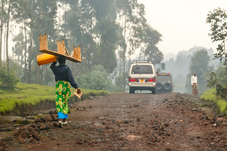 Rwandan woman in colorful traditional cloth walikung and carrying bench on her head, Kigali, Rwanda