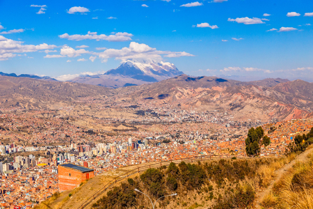 View to the snow cap of Illimani peak and valley full of living houses, El Alto, La Paz city, Bolivia