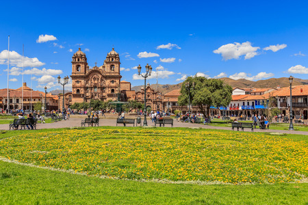 Plaza de Armas main square with cathedral and yellow flowers  in foreground, Cuzco, Peru