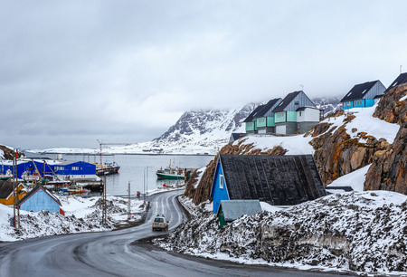 Acrtic road to the docks and port between the rocks with Inuit houses, Sisimiut, Greenland Banque d'images
