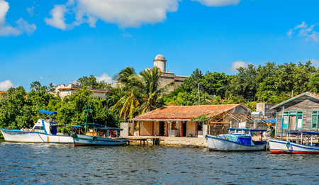 Cuban fishing boats and village houses with Jagua Spanish castle walls in the background, Cienfuegos province, Cuba