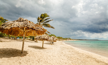 Rancho Luna sandy beach with palms and straw umbrellas on the shore, Cienfuegos, Cuba
