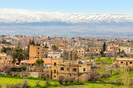 Lebanese houses in Beqaa Valley with snow cap mountains in the background, Baalbeck, Lebanon Imagens