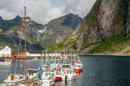 Yachts and boats with mountains in the background at pier in Reine, Moskenesoya, Lototen islands,, Nordland County, Norway