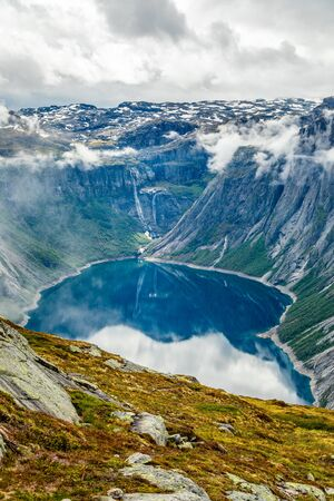 Blue lake surrounded by steep cliffs hiding in clouds, Odda, Hordaland county, Norway