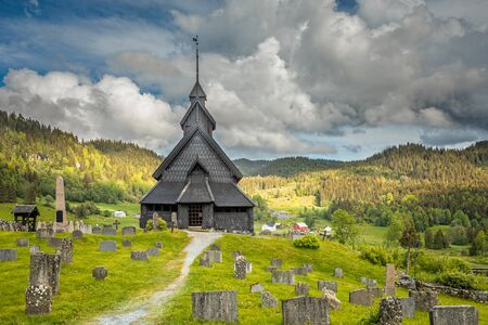 Eidsborg medieval wooden Stave Church and graveyard in front with green forest and cloud sky in the backround, Tokke, Telemark county, Norway Banque d'images
